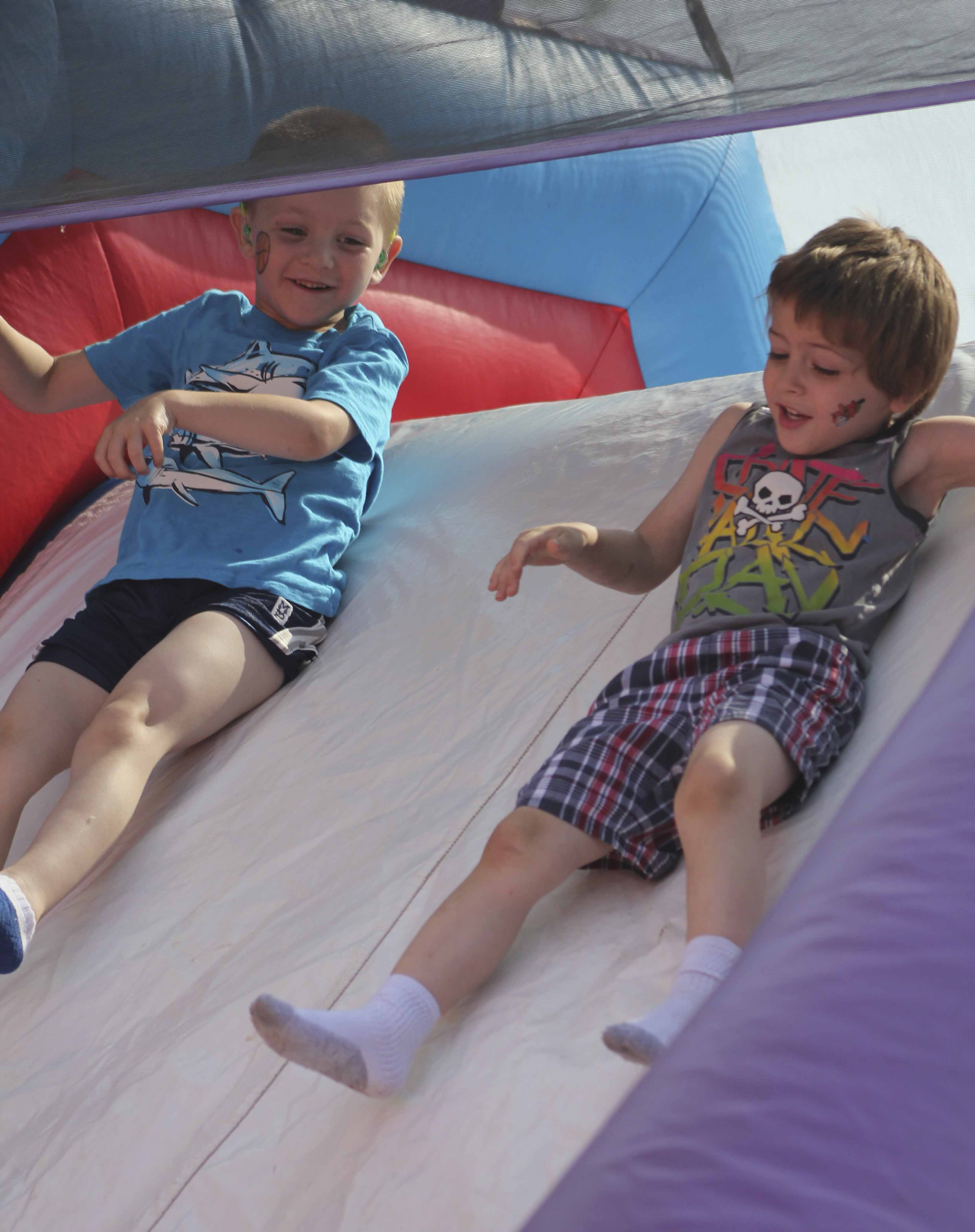 Monticello's elementary schools held their annual end of the school year Fun Day May 24. At Shannon, preschoolers Caden Bowers (left) and Reaver Mettler enjoy a trip down the inflatable slide. (Photos by Pete Temple)