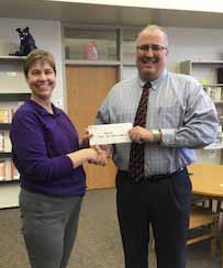 Ohnward Bank & Trust made a donation to the Monticello High School speech department to help offset costs of traveling to the All-State Speech Festival. Speech coach Kim Carlson (left) accepts the check from Pat Recker of Ohnward. (Photo submitted)