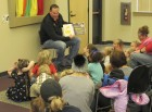 "Monticello Police Chief Britt Smith reads ""Monsters Love New Colors"" during the 1,000 Books Before Kindergarten kick-off. Smith's son, Colt, was also in attendance."