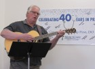 Dr. Philip First entertained the throngs of guests who showed up for his retirement reception on May 2 at MercyCare in Monticello. He wrote and performed a song about going into retirement after 40-plus years as a family physician. (Photo by Kim Brooks)