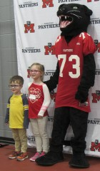 "Siblings Memphis and Roslynne ""Roz"" Russ pose for a picture with the Monticello School mascot, the Panther. Curriculum Director Gretchen Kriegel took photos of elementary students with the Panther throughout the evening."