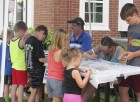 Library board member Joey Ellison and his daughter Danielle, help kids paint rocks to create their own tic tac toe game. There were several outdoor activities for families at the library's anniversary event.