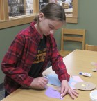 Paige Pumphrey puts together a scarecrow during the library's Fall Festival.