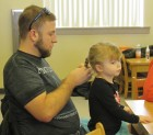 "Ben Turnis and his daughter Reagyn attended the library's ""Daddy & Daughter Hair Workshop."" Reagyn sat very still as her dad braided her short hair."