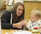 """Mary Intlekofer and son David work together on a holiday craft during the library's """"Cookies & Cocoa"""" party."""