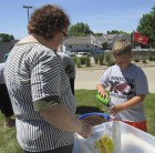 Librarian Penny Schmit assists Porter Campbell in filling his cup with gardening dirt. Following Olson's program, the kids went outside to plant wildflowers.
