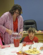 Library Director Michelle Turnis pours water and punch for Annie Schlarmann at the library's tea party on Feb. 11. Those in attendance included moms, daughters, sons, grandmothers, grandchildren, aunts, nieces and nephews.