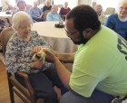 """MNRC resident Ruth Ehrisman pets a guinea pig named """"Orville"""" as Moorer takes him around to the residents. Camp Courageous owns two guinea pigs, brothers named """"Orville"""" and """"Wilbur,"""" named after the famous Wright brothers."""