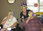 MNRC residents David Cavey and Delores Neal pose for a fun Mardi Gras photo with Activities Director Heather Dudley. The center celebrated Mardi Gras on Feb. 28. (Photo submitted)