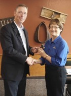 Outgoing Monticello Rotary President Eric Briesemeister hands over the gavel to new Rotary President Audrey Savage. The new president's term began on July 1. (Photo submitted)