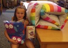 """Paige Pumphrey was the library's Summer Reading Program winner of a gift set donated by Monticello Canoe Rental. The prize included a canoe rental gift certificate, a pillow bed, an owl blanket, and the """"Owl Diaries"""" book set."""