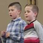 Sacred Heart first-graders Hayden Hackney and Wyatt Wilson belt out a song during their Dec. 15 Christmas program.