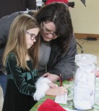Chloe Cozad gets some help from her grandmother, Karen Brokaw, as she votes for her favorite decorated Christmas tree at the Tree Walk.