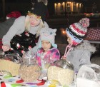 Reese Cox assists Evelyn and Amelia Tobiason in making reindeer food during Christmas on the corner.