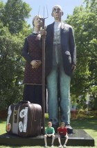 Anamosa youth Archie Boffeli, 9, and Carson Wild, 11, demonstrate just how tall the statue is. The artwork will be on display through next spring.