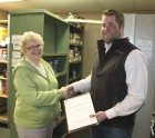 The Jones County Cattlemen donated a stack of checks totaling $200 worth of beef products to the Monticello Food Pantry March 31. Marilyn Schneiderman, a member of the food pantry's steering committee, accepts checks from Cattlemen board member Neal Grant. (Photo by Pete Temple)