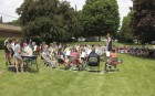 A large crowd on a sunny but windy day watches the Concert on the Green.