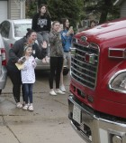 Anabella Husmann of Monticello (front, in white) waves at a Monticello Fire Department truck with her mother, Amanda. Fire trucks passed by Anabella's home on Monterey Trail May 18 to help her celebrate her seventh birthday. Also looking on are Skyleigh Husmann (in black), Kaylin Noll and Alyvia Husmann (far right). (Photo by Pete Temple)