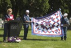 Kim Tauke (far left) speaks about the Quilts of Valor that are available. One of the quilts is being held up by Denny Fear (right) and Dennis Gray.