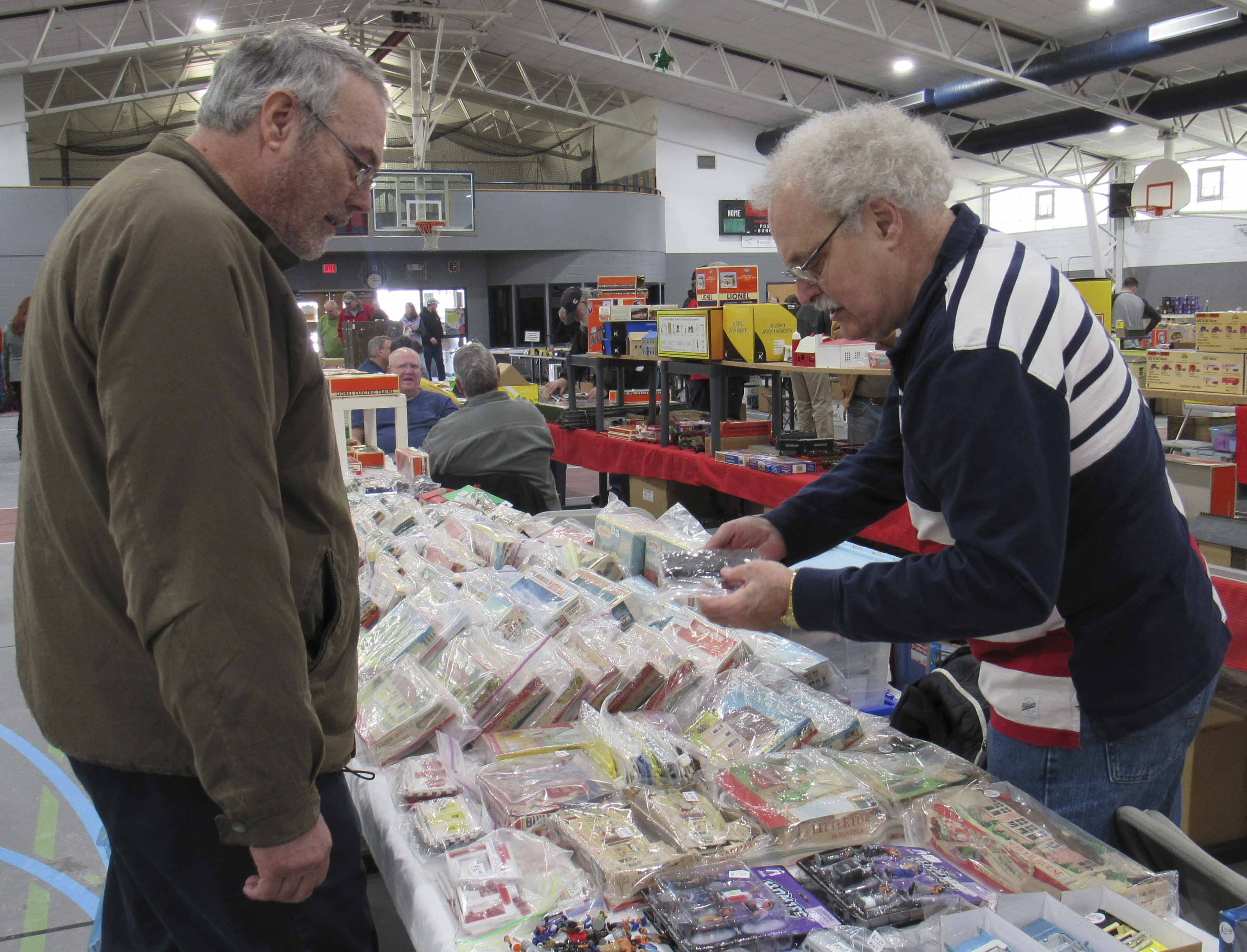 John Niehaus (right) of Ankeny showcases his Plasticville Collectors Association sets. The plastic train village sets have been around since the mid-1940s. Wayne Vorwald of Farley reminisces about the pieces from his own childhood.